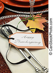 Beautiful Autumn Fall theme Thanksgiving dinner table place setting with Happy Thanksgiving tag attached to silverware. Close up on message,