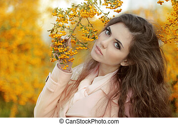 Beautiful  Autumn Girl Portrait. Trendy young Woman over yellow leaves in the autumn park. Outdoor photo.