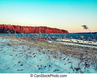 Beautiful autumn landscape. The first ice and snow on a forest lake in the sunset