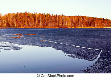 Beautiful autumn landscape. The first ice on a forest lake in the sunset