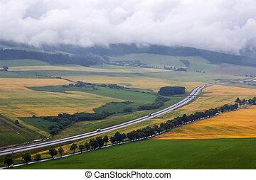 Beautiful autumn mountains landscape, road in  fields, cloudy sky