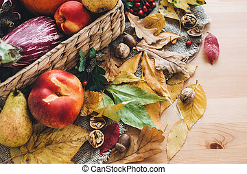 beautiful autumn pumpkin and vegetables in basket and colorful leaves with acorns and nuts on wooden table, top view. Fall bright image. Harvest time. Happy Thanksgiving