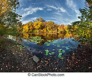 Beautiful autumn sunset at the river in the forest with clouds i