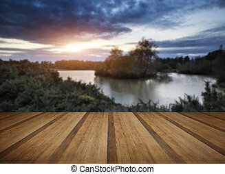 Beautiful Autumn sunset over lake landscape in forest with wooden planks floor