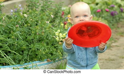 Beautiful baby boy playing with a plate for frisbee.