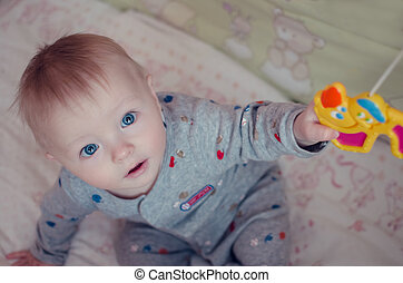 Beautiful baby boy sitting and plaing with crib mobile toy