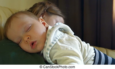 Beautiful baby boy sleeping in mother arms, close up