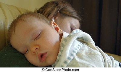 Beautiful baby boy sleeping in mother arms