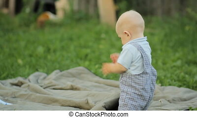 Beautiful baby boy standing on his feet and falls on ass in the garden