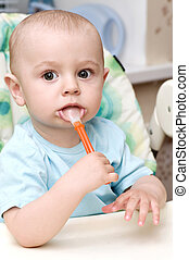 Beautiful baby boy with spoon