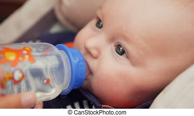Beautiful baby drinking water from bottle