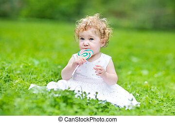 Beautiful baby girl eating candy - Beautiful baby girl with...