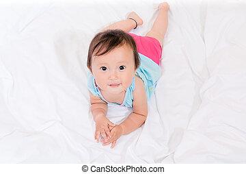 Beautiful  baby girl  happy lying on bed white bedsheet