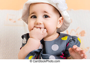 Beautiful baby girl in hat and dress