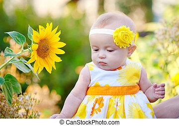 beautiful baby girl near yellow sunflowers on field.