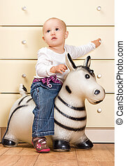 Beautiful Baby Girl on a toy Horse