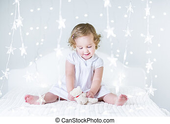 Beautiful baby girl playing with her toy bear on a white bed...