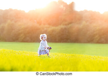 Beautiful baby girl running in a field on a sunny autumn evening