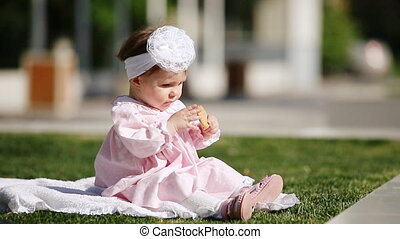Beautiful baby-girl seating on the green grass and eating bake in the park.