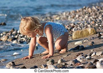 Beautiful baby girl sitting on the beach