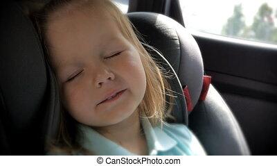 Beautiful baby girl sleeping in car seat