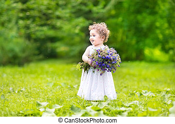 Beautiful baby girl with curly hair carrying flowers in a...