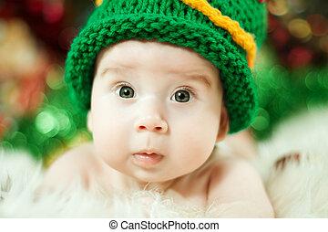 beautiful baby in green knitting hat closeup portrait