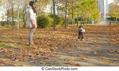 Beautiful baby is playing in autumn park with her mother about fallen leaves. A child plays with a white soccer ball, the boy about a year