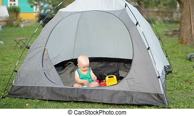 Beautiful baby is playing with a large tent on the grass. Baby less than a year, in a green t-shirt and toys inside the tent.
