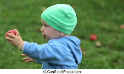 Beautiful baby is walking around in the garden with apple at home. Kid in hat and sweater on a grass background
