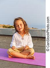 Beautiful baby on the yoga mat