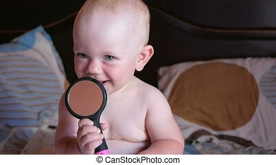 Beautiful baby playing with comb on the bed. Smiles and...