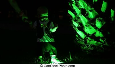 Beautiful Baby playing with green backlight palm trees at night. The unusual silhouette of a baby