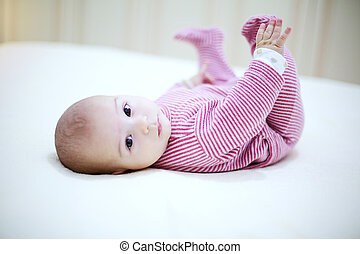 Beautiful baby playing with his legs on the bed in bedroom