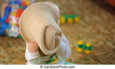 Beautiful baby trying to eat his hat. The boy is less than a year