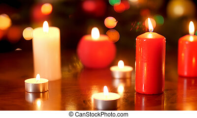 Beautiful background for Christmas celebrations with burning candles on wooden table against Xmas tree
