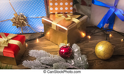 Beautiful background for winter holidays and celebrations. Christmas gifts and colorful bauble lying on wooden desk