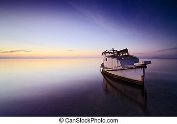 Beautiful background of sky and sea at sunrise with a little old boat