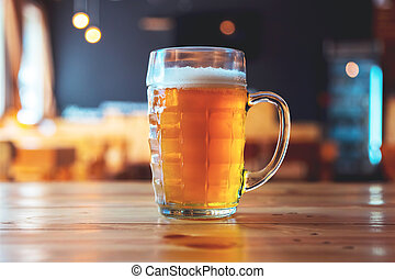 Beautiful background of the Oktoberfest. Glass of cold fresh lager beer on a wooden bar counter in pub with free space for your text
