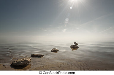 beautiful background stones in clear blue water against the sky
