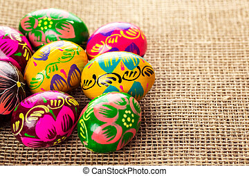 Beautiful background with Easter eggs laid out on a burlap background with free space for your text
