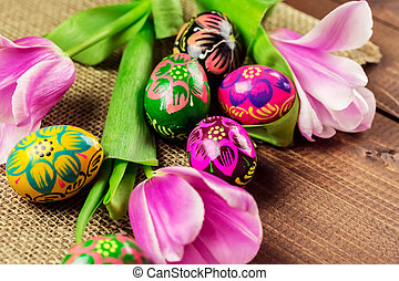 Beautiful background with painted Easter eggs and tulips laid on a background of burlap and old brown boards with free space for your text