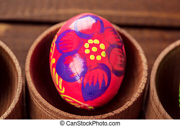 Beautiful background with painted Easter eggs in little wooden nests laid on a background of old brown boards with free space for your text