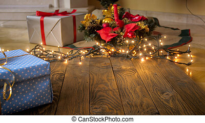 Beautiful background with wooden boards against glowing Christmas lights, gift boxes and baubles. Perfect for winter celebrations