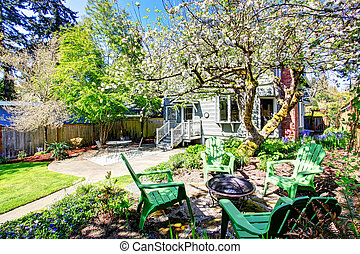 Beautiful backyard view with two patio areas and blooming trees.