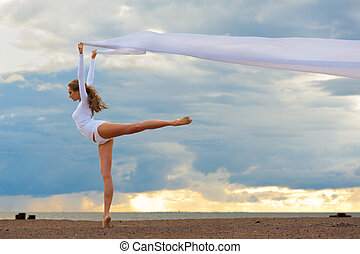 Beautiful ballerina dancing at the sea beach.