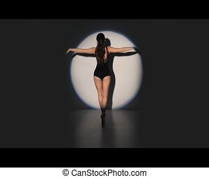 Beautiful ballerina dancing in spotlight
