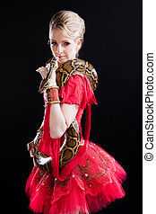 beautiful ballerina girl in a red scenic dress with  python on black