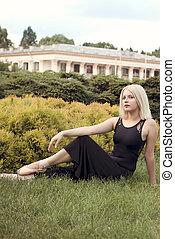 Beautiful Ballerina in pointe gracefully sitting