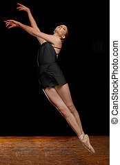 Beautiful Ballerina Leaping in Studio on Black Background